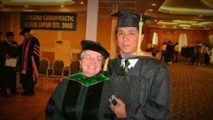 卒業式の会場で教授と記念撮影